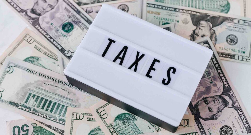 """Sign """"Taxes"""" on top of dollar bills - Polaris Consulting"""