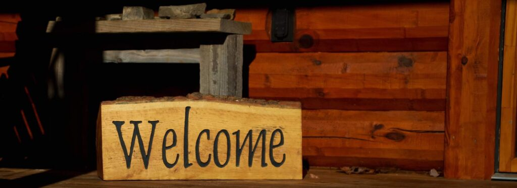 Welcome sign against log cabin wall - Polaris Consulting